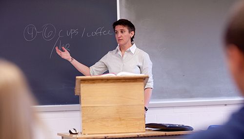 Lecturer standing in front of a podium, lecturing a class.