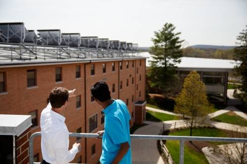 Two students looking across campus from the top of a building.