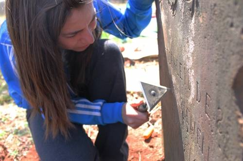 Student cleaning a gravestone at Asper Burial Ground