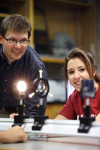 A professor and student observing the outcomes of a light ray experiment.