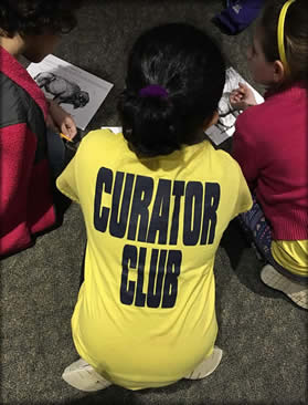 A child wearing a curator club tee shirt.