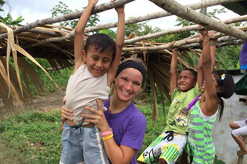 A student from AROMA mission trip holding up a child on a monkey bar.
