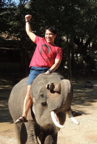A male student riding an elephant in Thailand.