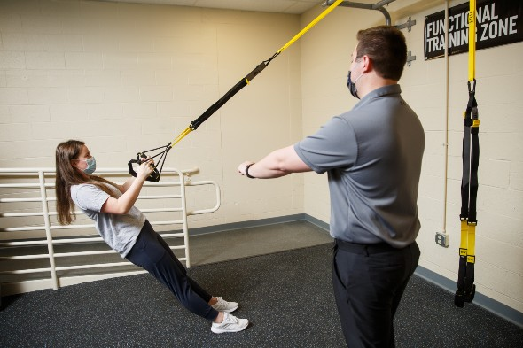 A female student in an athletic training facility does pull-ups on ropes while an instructor watches.