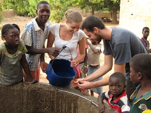 A group of African children surrounding a well.