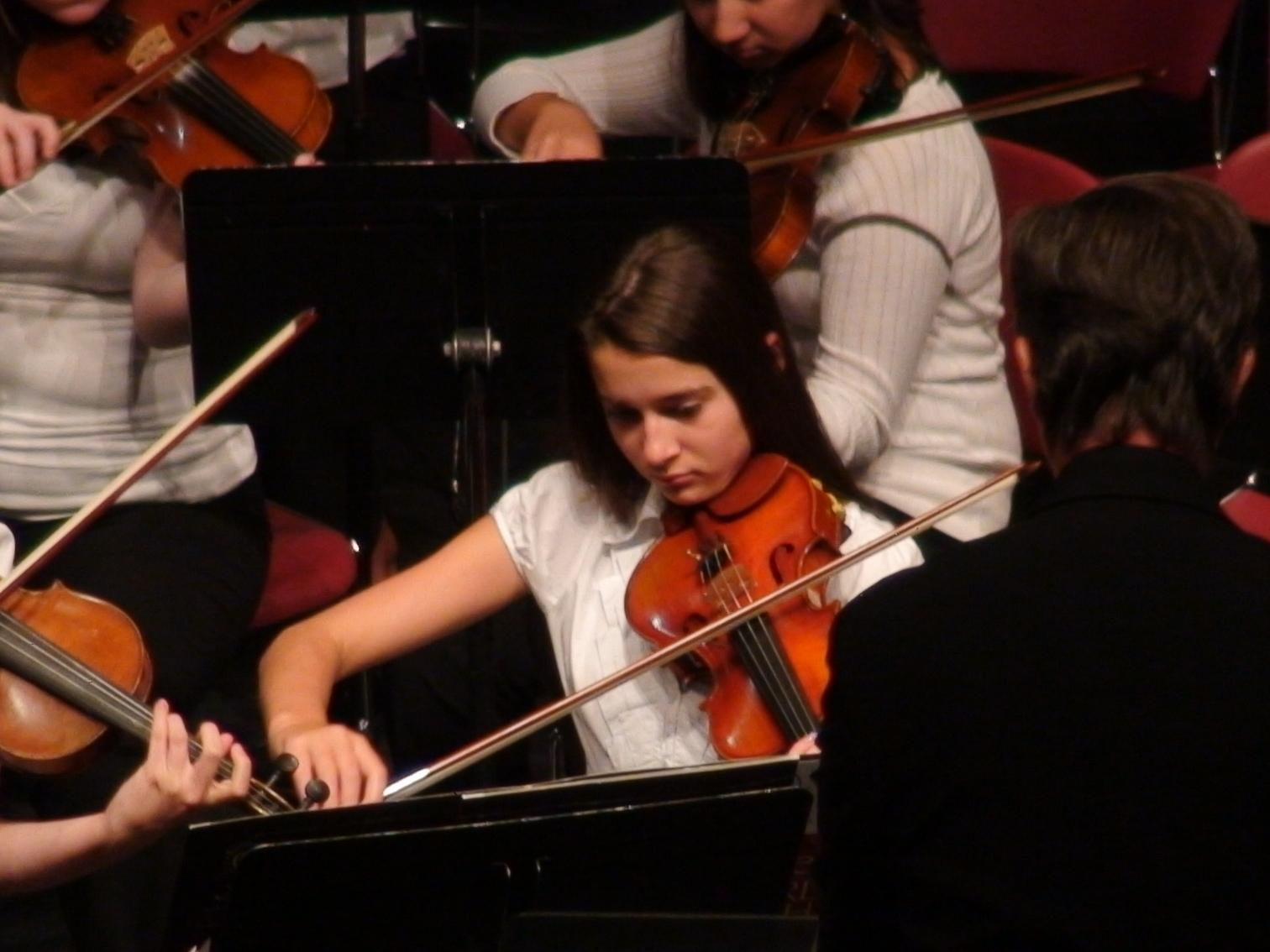 A female violinist in an orchestra.