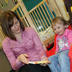 Teacher with a girl at the Early Learning Center.