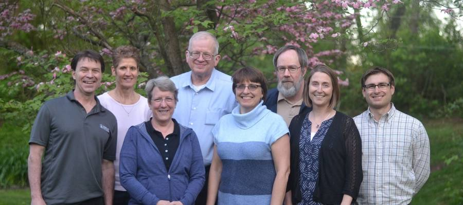 A group photo of the chemistry department at Messiah College, standing in front of a blossoming tree.