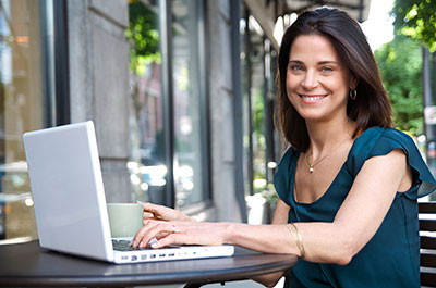 Young woman at laptop computer sitting outside working