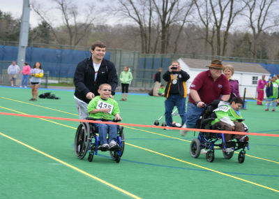 Volunteers pushing children in wheelchair during Special Olympics.
