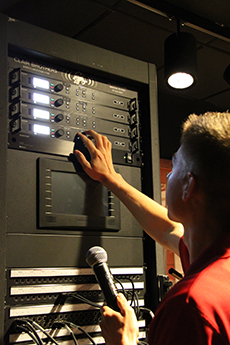 A male student adjusting volume levels of the audio system.