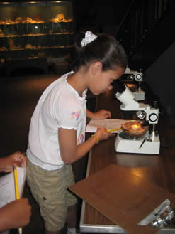 A girl looking through a microscope.