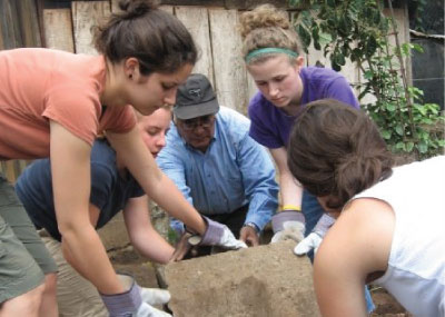Students from Agapé center working together to move dirt from a field.