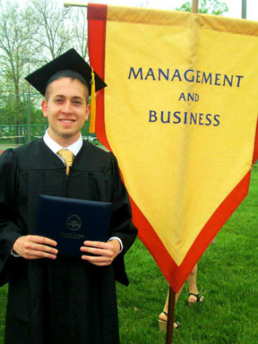 Jordan in front of the business banner at graduation