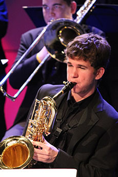 A male student playing a saxophone.