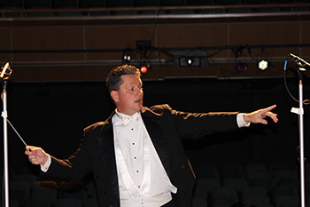 A conductor passionately conducting his orchestra.