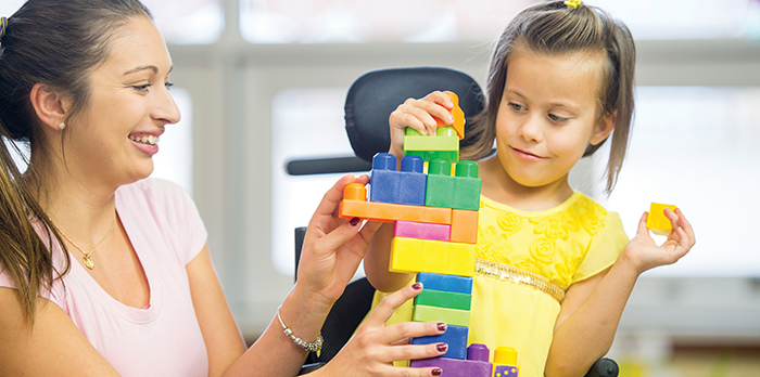 handicapped girl plays with building blocks