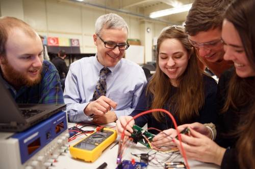 Students and a professor working on an engineering project.