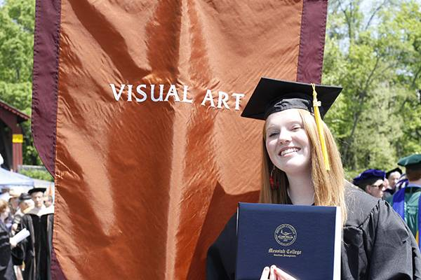 Graduate standing by visual art banner at commencement