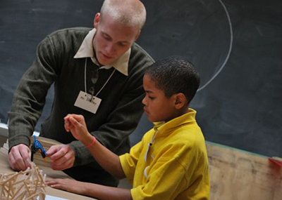 A college student teaching a young child how to make three dimensional sculptures.