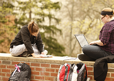 Students sitting outside on a brick wall and studying.