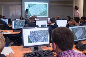 Students sit behind laptops that display images of historic maps.