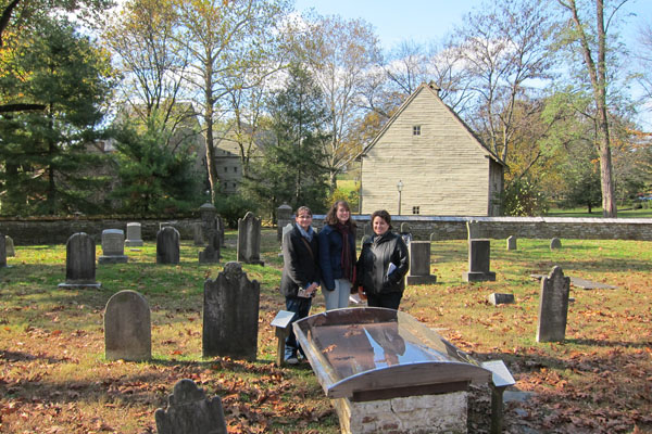 Three women standing at a cemetery.