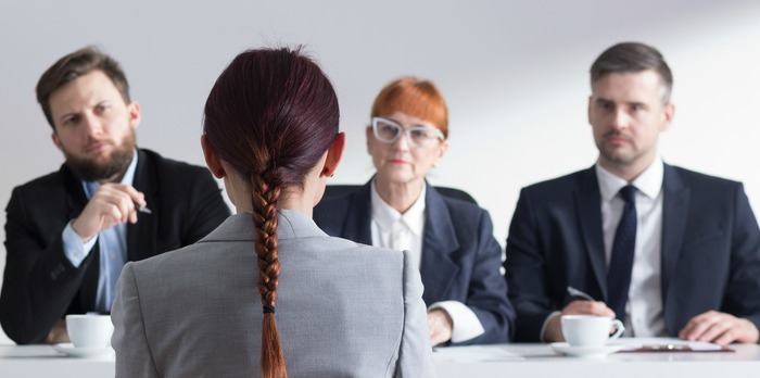 Three employers interviewing an an applicant.