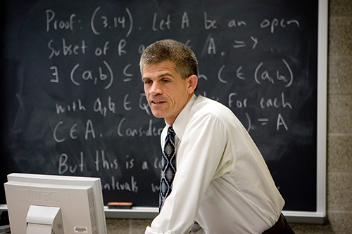 A math professor standing in front of a filled black board.