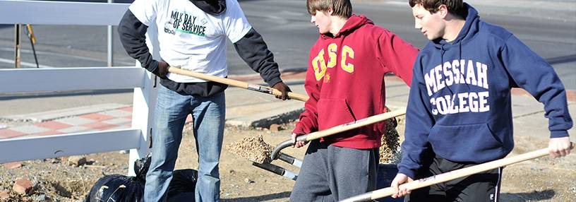 Students with shovel helping at a service trip.