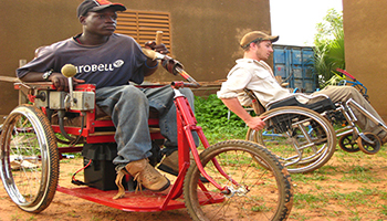 People on a tricycle built for the disabled by the Collaboratory.