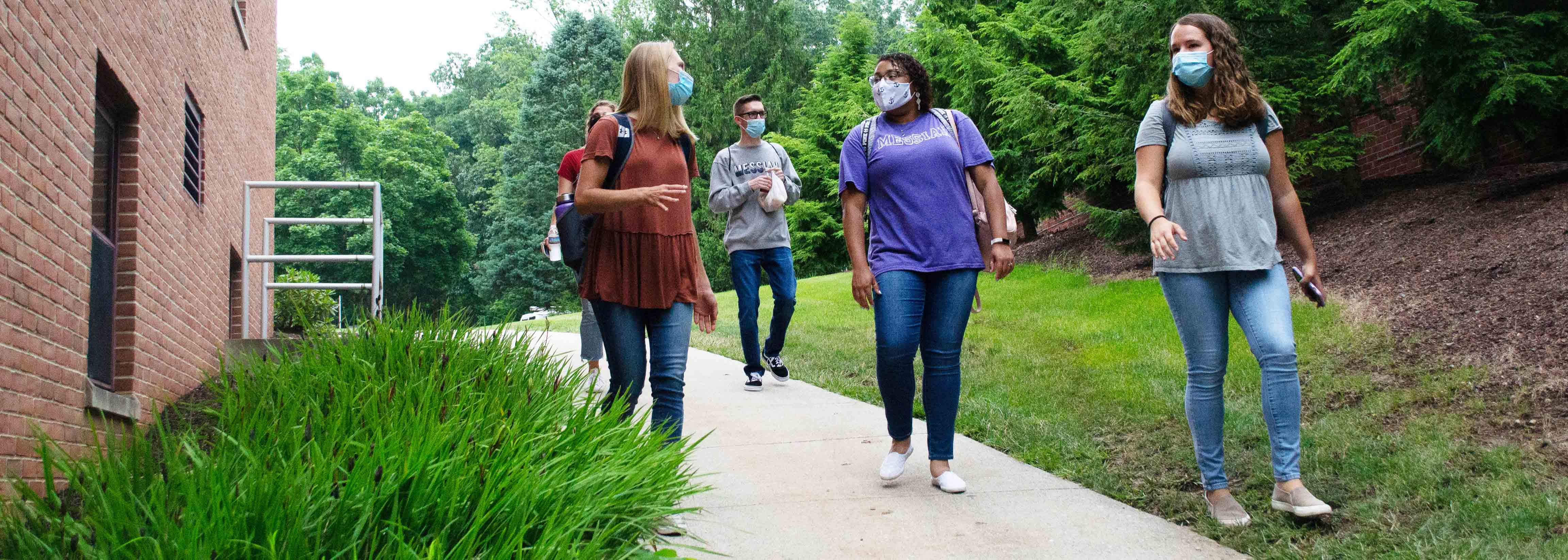 students in masks walking near a residence hall