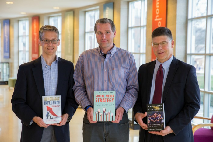 Business professors holding their published book.