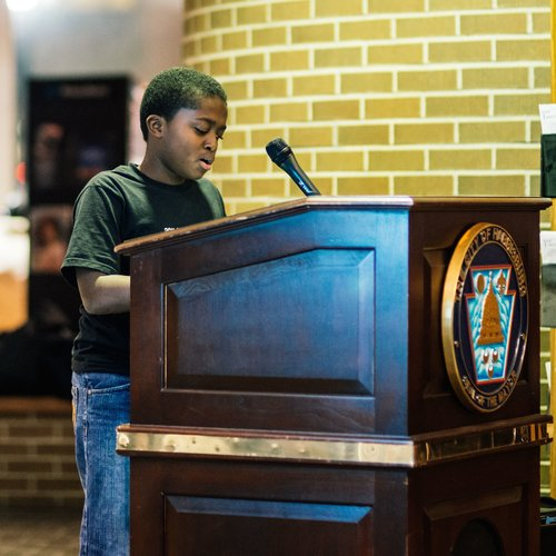 A student reads his poem at the 2015 Poetry Celebration