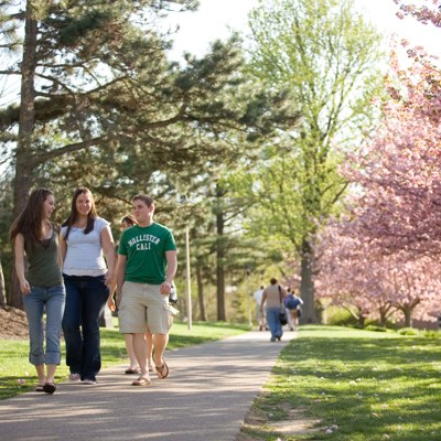 Students walking down the sidewalk in the spring on campus
