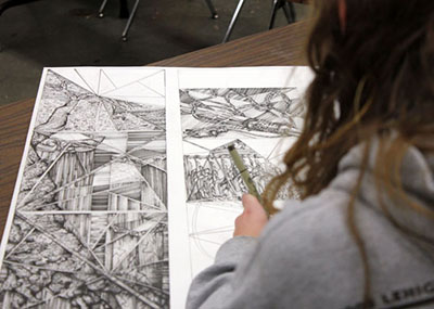 Student drawing two dimensional art.