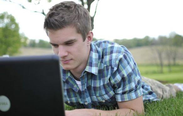 Male student with laptop outside.