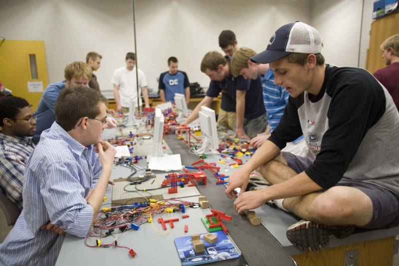 Engineering students putting together a large Lego project around a table