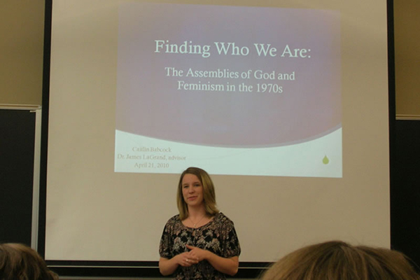 A woman giving a presentation about feminism and faith.