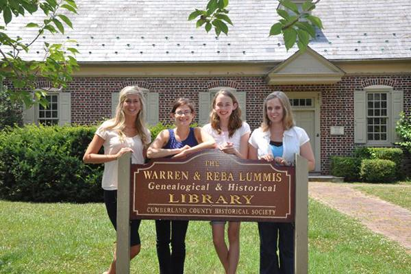 Four women standing in front of a sign of Warren and Reba Lummis Genealogical and Historical Library.