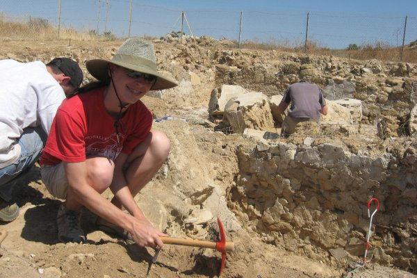 A student excavating the ground using a pickaxe.