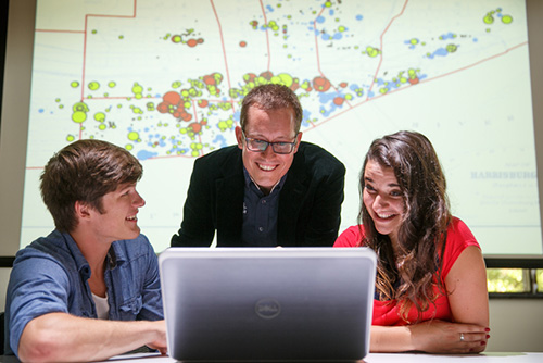 A professor and two students working together in front of an image of a map on the projector.