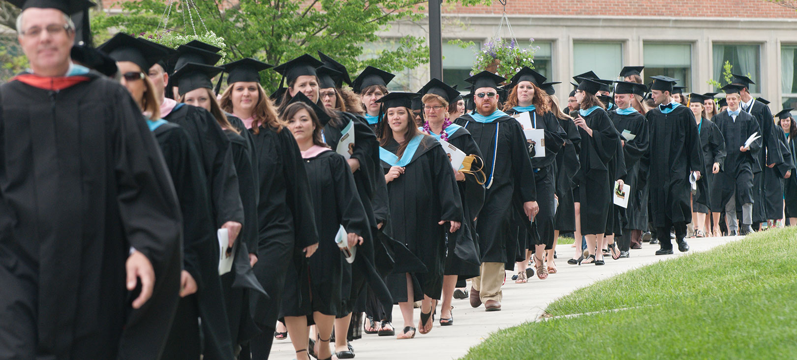 Financial Aid for Graduate Programs Graduating seniors walking with their gowns and caps on.jpg